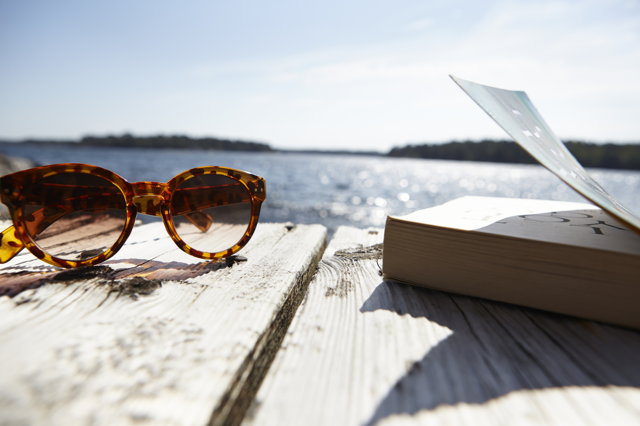 sunglasses-and-book-on-wooden-jetty-close-upjpg