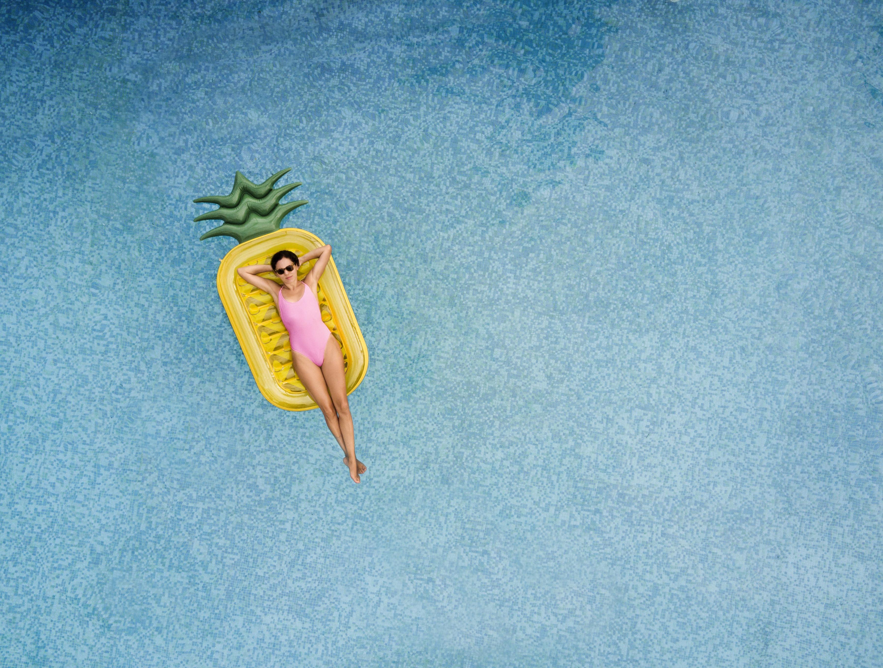 unbeschwerte-frau-auf-aufblasbare-ananasjpg