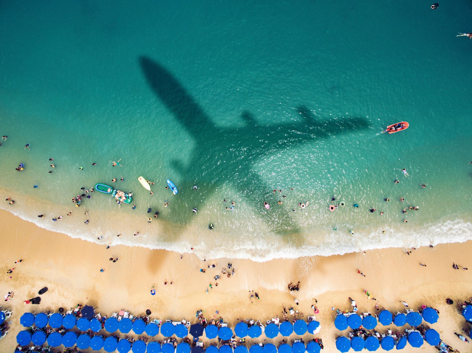 airplane-s-shadow-over-a-crowded-beachjpg