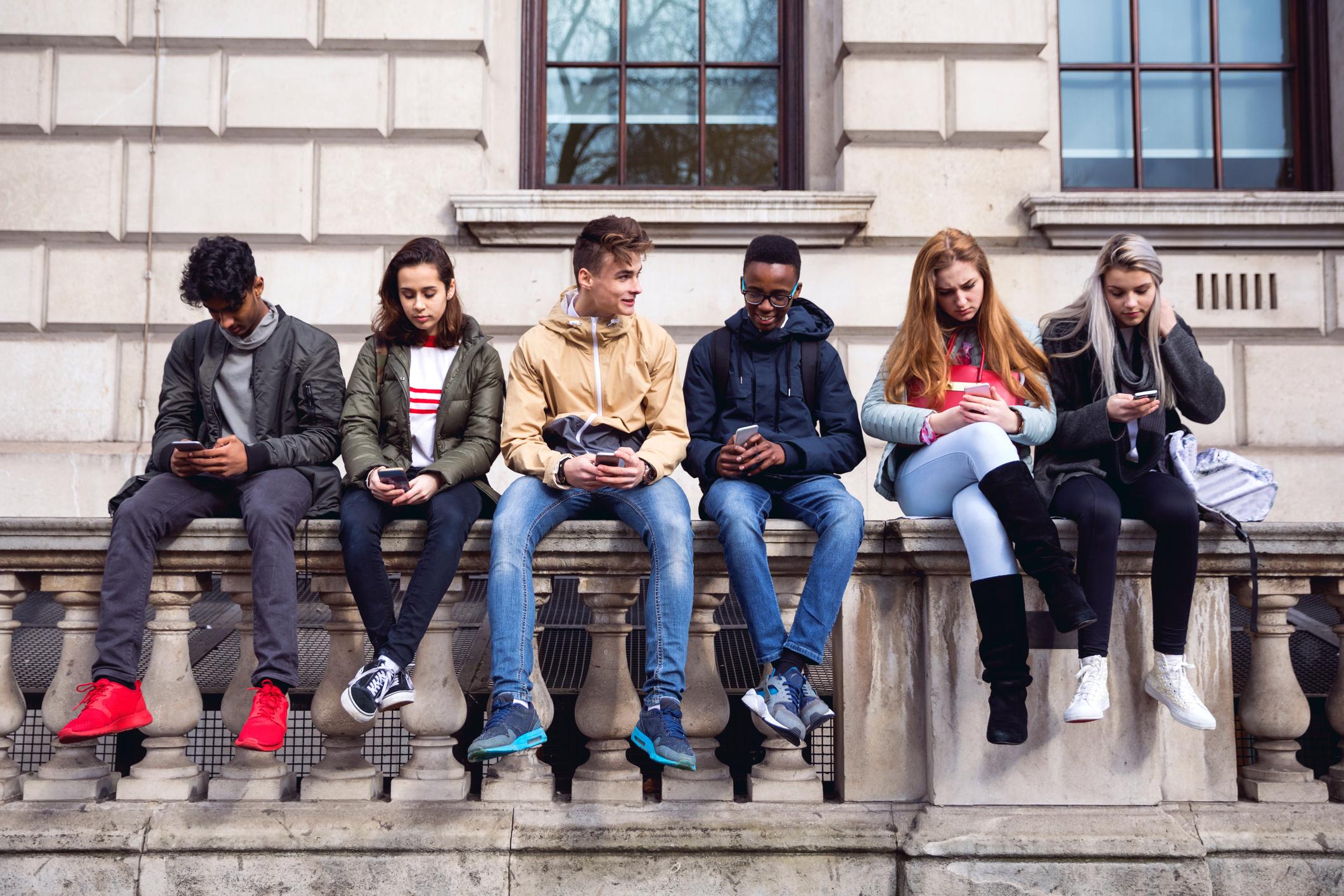 jugendliche-sch-ler-mit-smartphone-auf-eine-schule-pausejpg